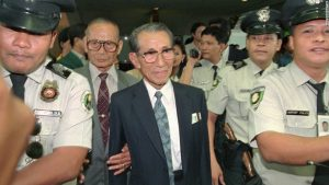 Former Japanese straggler Hiroo Onoda, center, is escorted by police shortly upon arrival in Manila Monday, May 20, 1996 for a sentimental journey. Onoda, then a lieutenant in the Japanese Army, stayed hidden in the island of Lubang, 90 miles southwest of Manila for 29 years until his discovery and subsequent surrender in 1974. Onoda will revisit his hiding place for the first time since emerging from his jungle hideout 22 years ago. (AP Photo/Bullit Marquez)