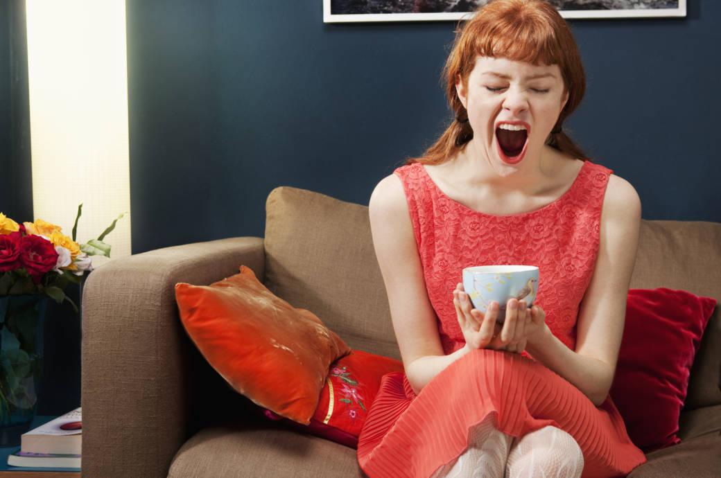 Жена, седяща на дивана, която се прозява