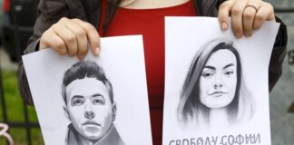 Жена държи портрет на опозиционния журналист Роман Протасевич и приятелката му София Сапега по време на протест на солидарност с Роман Проташевич в беларуското посолство в Рига, Латвия, 25 май 2021 г.