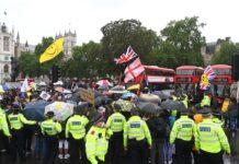 Протестиращи срещу локдауна държат плакати, докато се събират в Уестминстър в Лондон, Великобритания, 21 юни 2021 г.
