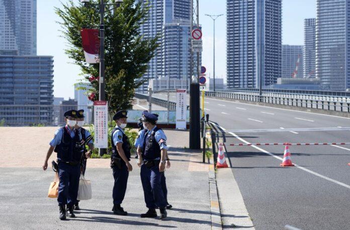 Полицейски служители пред Олимпийското село (вижда се на заден план) в Токио, Япония, 17 юли 2021г.