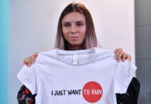 """Кристина Tимановская показва тениска с надпис """"Просто искам да бягам"""", по време на пресконференция във Варшава, Полша, 05 август 2021г."""
